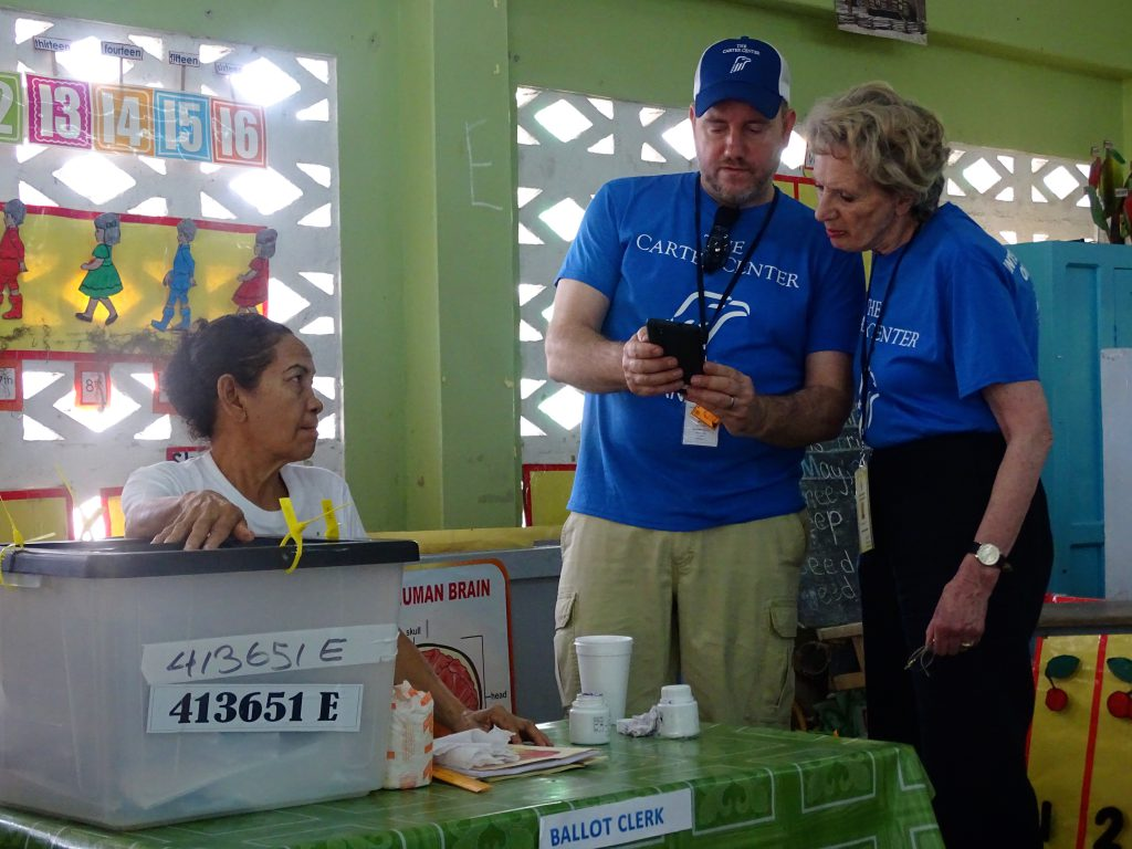 Carter Center observers in Guyana complete a checklist as a polling official looks on.