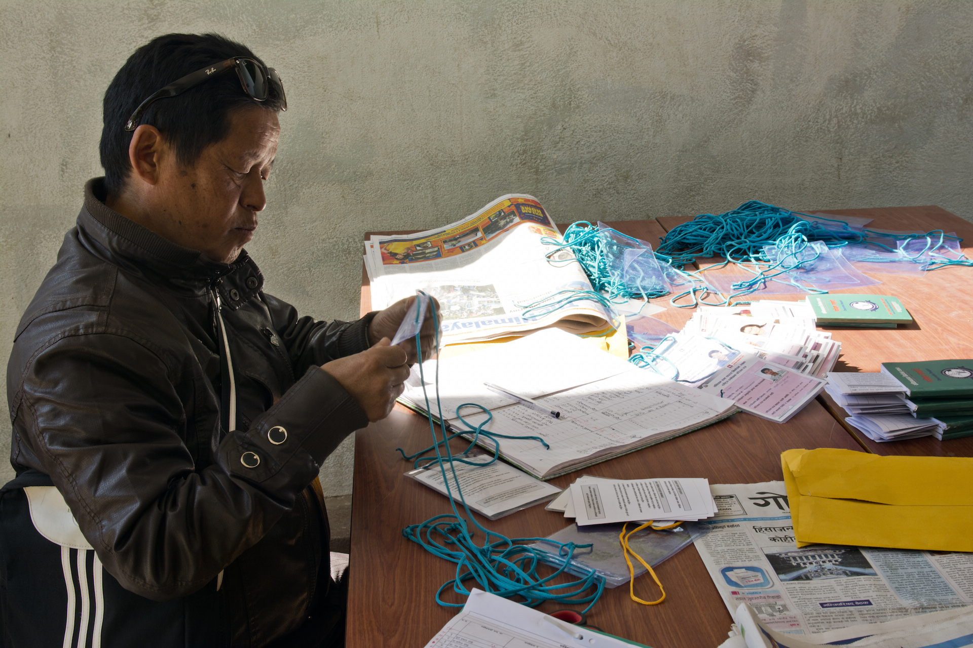 At the National Election Observation Committee, a domestic election observation organization based in Kathmandu, a worker hands out observer credentials.