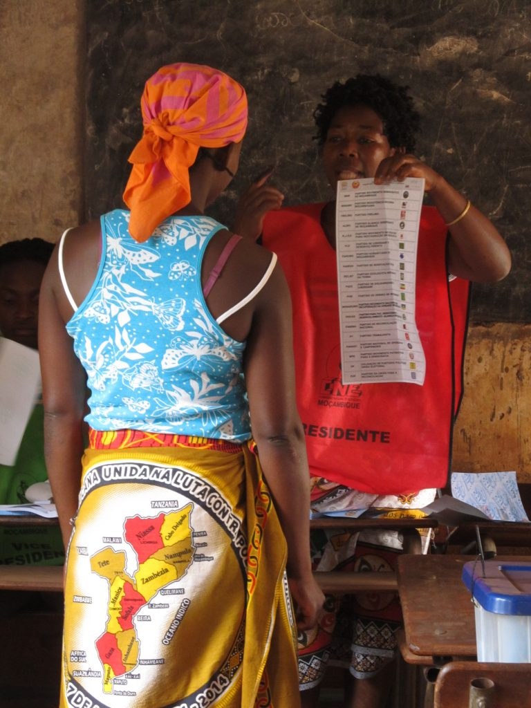 A presiding officer in Gurue city, Zambézia province, explains procedures to a voter, showing her a sample ballot.